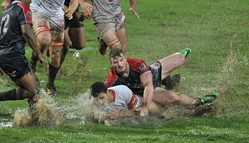 FNB NMMU's Christopher Cloete tackles FNB Tuks's Jade Stighling during their rain-soaked FNB Varsity Cup clash in Pretoria on Monday night. Photo: Wessel Oosthuizen/SASPA